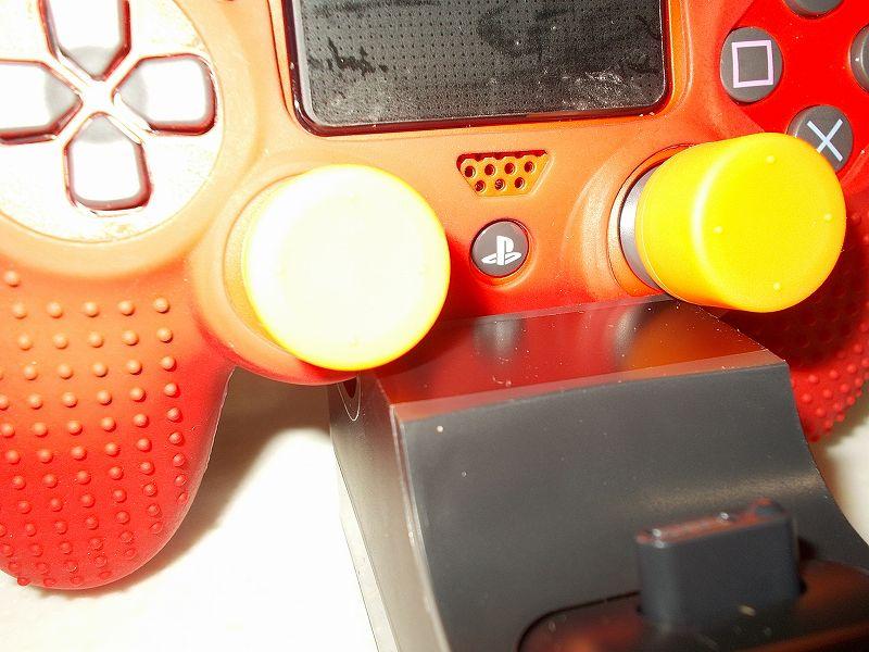 DUALSHOCK 4 ワイヤレスコントローラーの購入と操作を快適にする便利なアイテムをまとめてそろえてみました、PS4 コントローラー用アナログスティックカバー オレンジ 購入、DUALSHOCK 4 ワイヤレスコントローラー マグマ・レッド CUH-ZCT2J11 の左右アナログスティックに高さ 15mm アナログスティックカバー装着後、DUALSHOCK 4 充電スタンド CUH-ZDC1J に取り付けた状態でのアナログスティックカバーの干渉状態